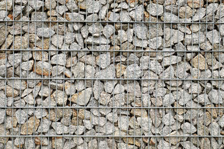 A wall made of gabions, next to it a bench and a garbage can. Garden architecture.