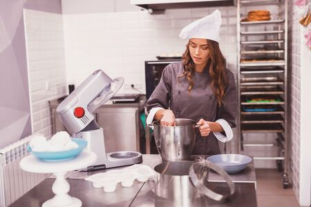 People, lifestyle, healthy eating, cooking and dieting concept. Positive young female chef preparing cream for desserts 版權商用圖片