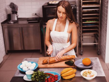 Young sexy woman cutting bread in kitchen. Stock Photo