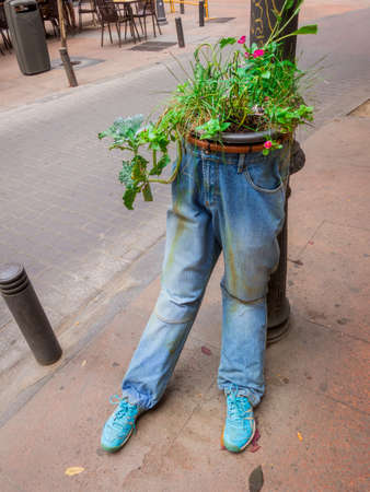 Flower pots in jeans on the street to protect places from people who misuse space