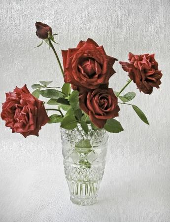 rose in crystal vase on light background photo