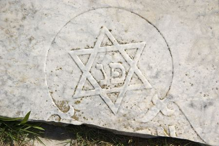Worn Star of David on old marble tombstone Banco de Imagens