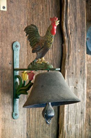 Vintage bell with rooster on grunge wooden wall photo