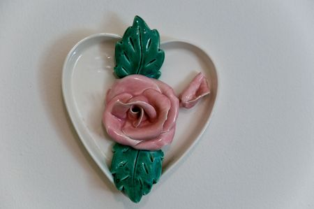 magnificence: Antique china flowers and heart shaped saucer on wall