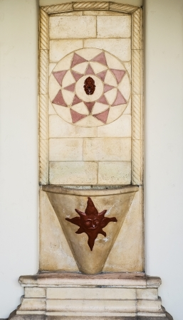 Spanish style colorful tile fountain on stucco wall  photo