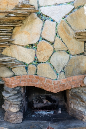 stone fireplace: Outside fireplace decorated with colorful stones