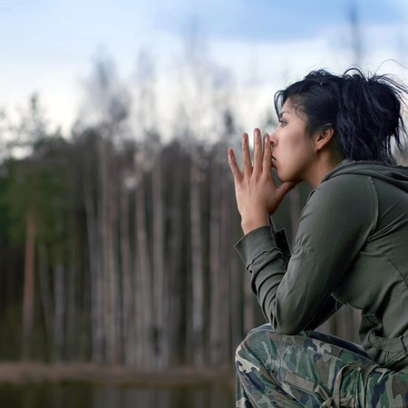 contemplation: East girl in a camouflage on coast of lake. Stock Photo