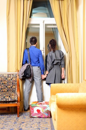Man and the woman look out of the window in a hotel room.  photo