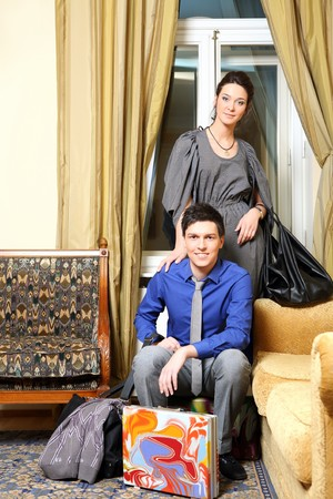 In a hotel room the smiling man sits on a suitcase, the woman behind it holds a bag in a hand.  photo