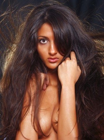 Magnificent bared suntanned girl covers a breast with hands. photo