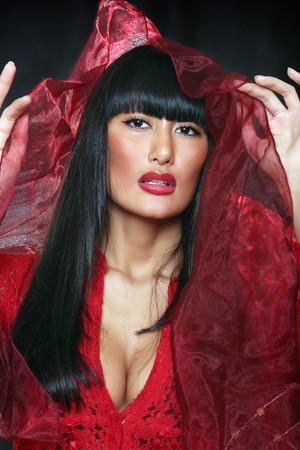 Beautiful east girl in a red dress lifts over the face a veil photo