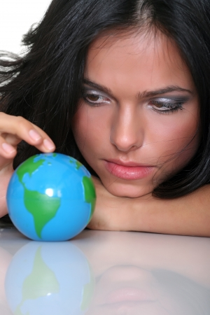 Beautiful girl and small globes, isolated on a white background  photo