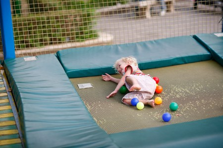 overwhite: Little boy on a childrens playground on a trampoline Stock Photo