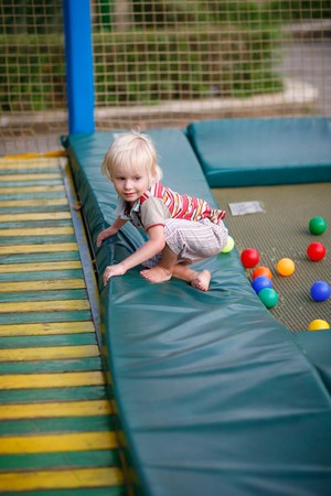bounce: Little boy on a childrens playground on a trampoline Stock Photo