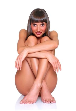 Beautiful naked girl sits having pressed to itself of a foot Stock Photo - 4592350