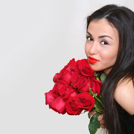 Portrait of the beautiful girl with a bouquet of scarlet roses. Stock Photo - 4592312