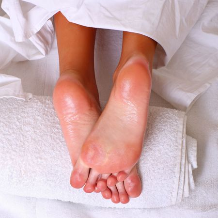 Well-groomed heels of female feet after processing of a skin by oil on a white towel photo