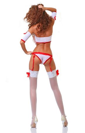 Slim young girl with red hair in red-white underwear costs a back to the photographer, isolated on a white background