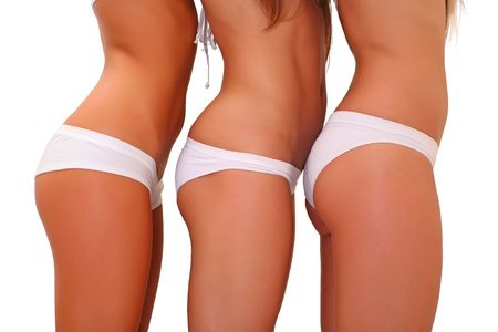 Three harmonous suntanned young women in a profile, in white underwear Stock Photo