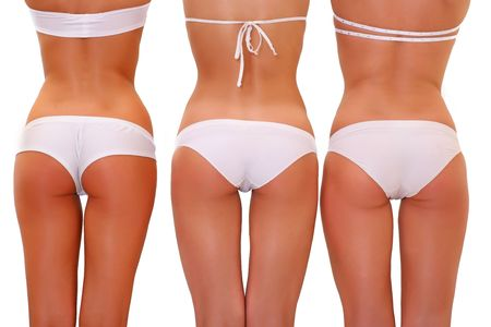 Three harmonous suntanned young women from a back in white underwear, isolated on a white background