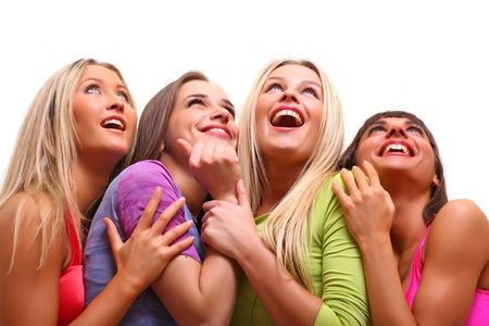 Four beautiful happy young women with a smile in bright multi-coloured clothes look upwards, isolated on a white background