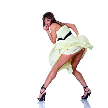 Joyful young woman in a dress turns around on an objective, isolated on a white background photo