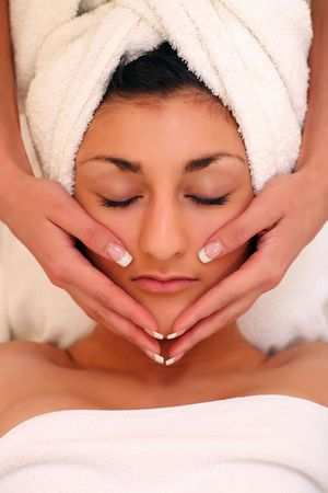 An attractive young lady getting a facial photo