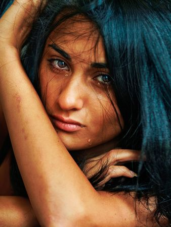 Emotional portrait of the beautiful young suntanned woman with scars on hands and tears on the face photo