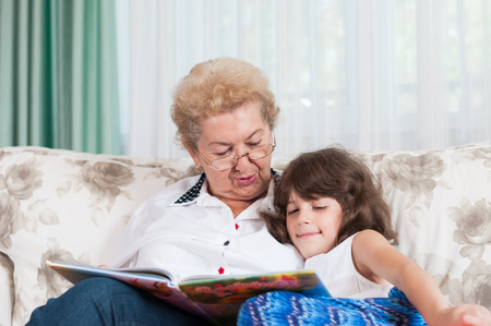 Nice elderly woman grandmother reading story to sweet young granddaughter photo