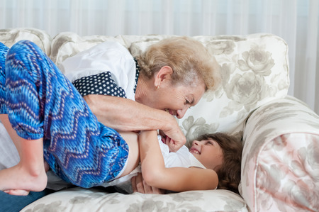 Nice elderly woman grandmother playing with sweet young granddaughter photo