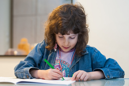 Little girl sitting at a table drawing and coloring in her book