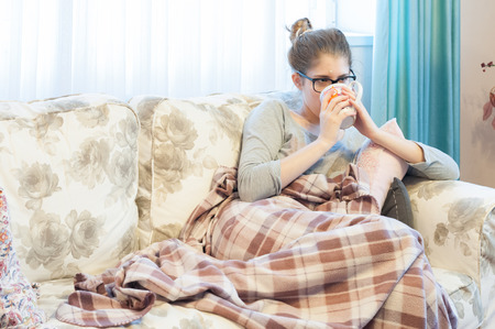 Sick young woman sitting on the couch and drinking tea Stok Fotoğraf