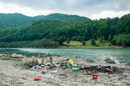 Pile of rubbish on lake shore polluting nature and beautiful landscape Stok Fotoğraf