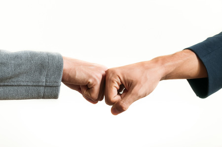 Two businessmen fist bumping against  a white background