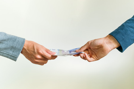 Two businessmen exchanging british money pounds sterling on white background