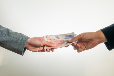 pounds money: Dos hombres de negocios que intercambian dinero brit�nico libra esterlina en el fondo blanco