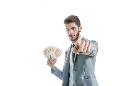 Successful business man holding money and pointing isolated on white Stok Fotoğraf
