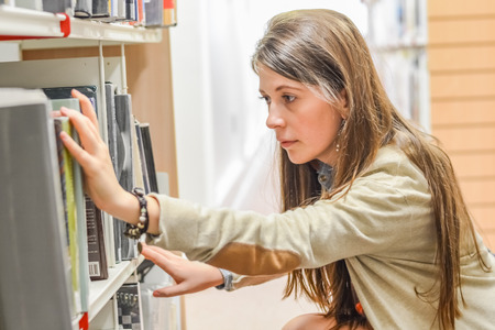 Attractive young female student searching for books in the library