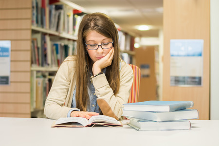Young woman reading books in the library. Female university student