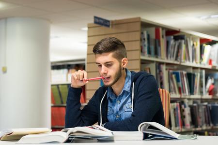 conocimiento: Buen aspecto masculino estudiante leyendo e investigando en la biblioteca. Estudiar para el examen Foto de archivo