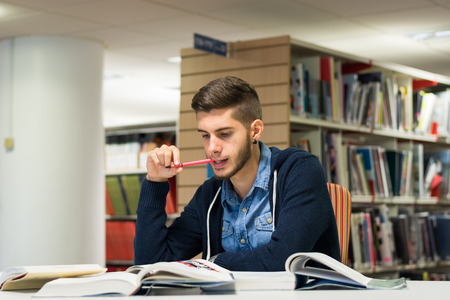 Good looking male student reading and doing research in the library. Studying for exam Stok Fotoğraf