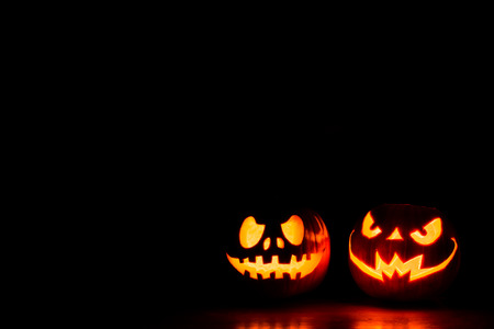 Scary Halloween pumpkins isolated on a black background with space for text. Halloween card concept. Stok Fotoğraf