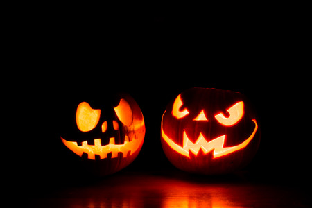 Scary Halloween Pumpkins Isolated On A Black Background. Scary Glowing  Faces Trick Or Treat Stock