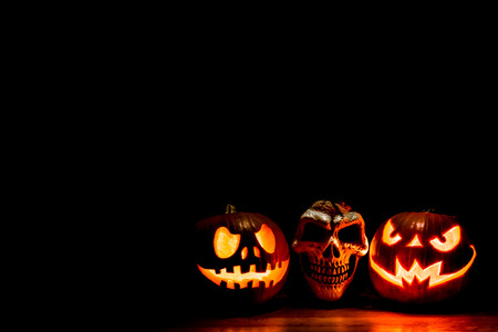 Scary Halloween pumpkins and skull isolated on a black background with room for text. Scary glowing faces trick or treat Stok Fotoğraf
