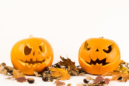 Halloween pumpkins with autumn leaves isolated on a white background with copy space for text. Scary faces concept Stok Fotoğraf