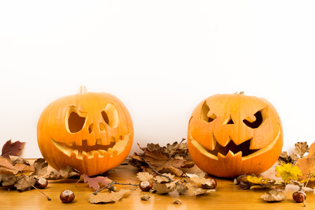 Halloween pumpkins with autumn leaves isolated on wood table with a white background and space for text. Scary faces concept