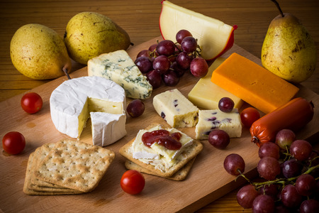 Delicious cheese platter with crackers and grapes on wooden board. Rustic cheese selection with fruit and vegetables
