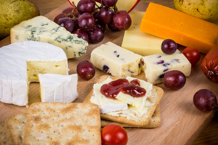 cheese board: Delicious cheese platter with crackers and grapes on wooden board. Rustic cheese selection with fruit and vegetables