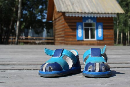 Blaue Kinderschuhe auf einem Holz