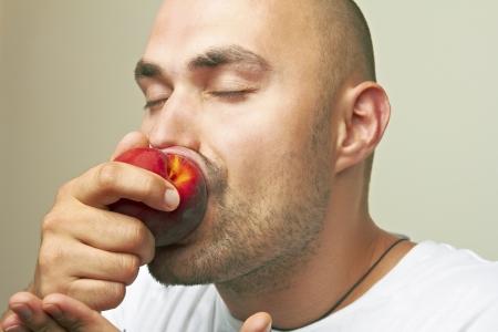 The man enjoying a peach